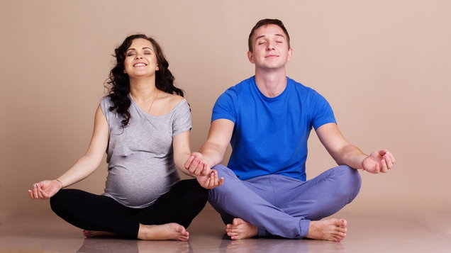 Pregnant girl and man doing yoga