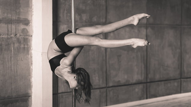 Pretty acrobat girl working out in the studio