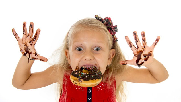 happy child showing dirty hands with stains of chocolate donut