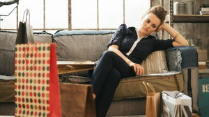 Tired woman sitting on couch among shopping bags in loft