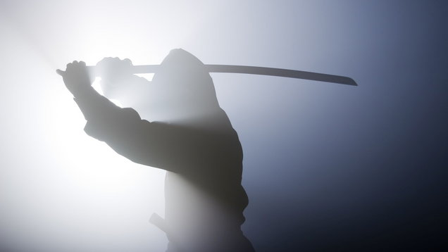 Silhouette of ninja swinging sword in fog