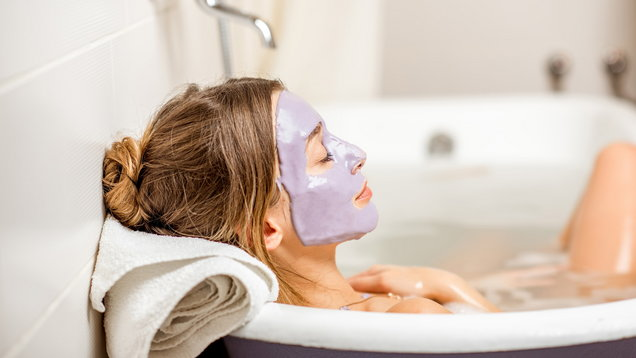 Woman with facial mask in the bathroom
