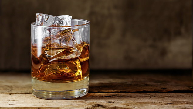 glass scotch whiskey with ice on a rustic wooden table