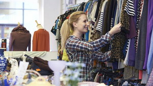 Female Shopper In Thrift Store Looking At Clothes