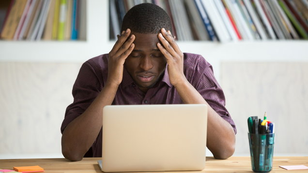 Frustrated black man feeling depressed after fail sitting with laptop