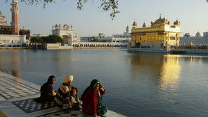 Pilgrims sit at the edge of a moat