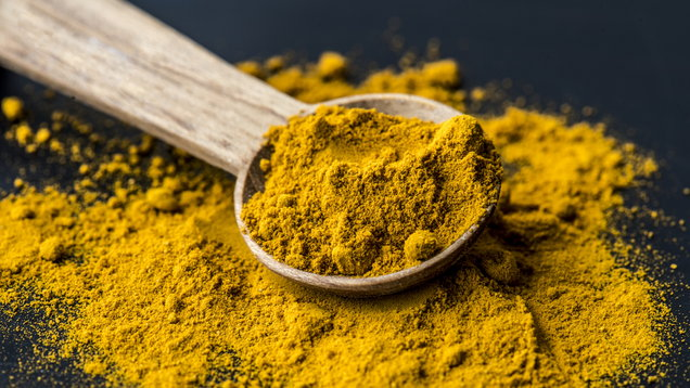 Closeup of tumeric powder spice on a spoon