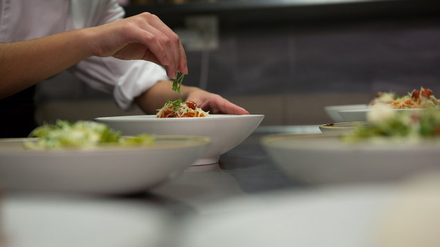 Close-up of chef garnishing meal on counter