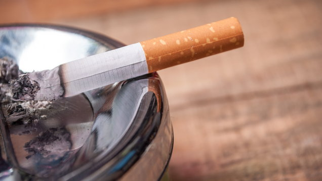 cigarette on ashtray on wooden background