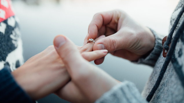 Picture of man putting engagement silver ring on woman hand