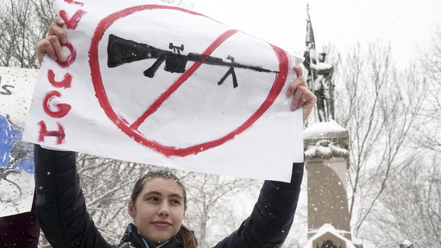 Student Marie Butler holds a sign in the snow with fellow students from high schools in Massachusetts