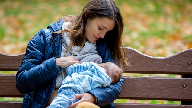 Young mother, breastfeeding her newborn baby boy outdoor in the park