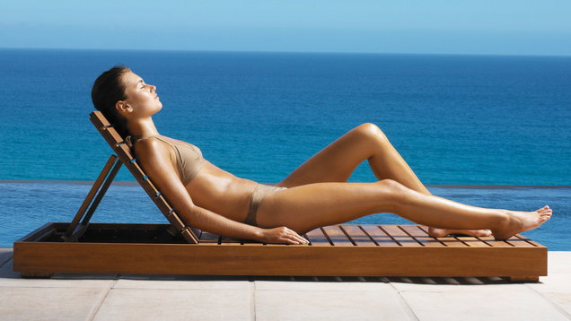 young woman sunbathing on deck chair side view