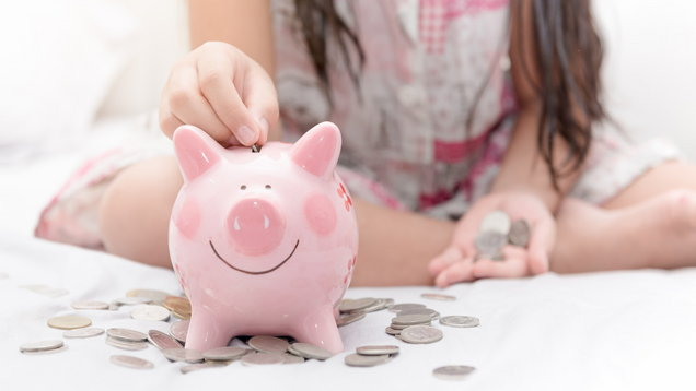 girl hand put money to piggybank on bedroom