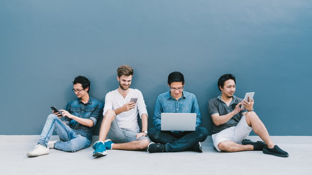 Multiethnic group of four men using smartphone, laptop computer, digital tablet together with copy space on blue wall. Lifestyle with infomation technology gadget, education, or social network concept