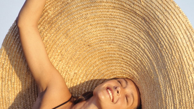 Young woman wearing large straw hat