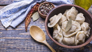 Homemade boiled dumplings of their dough and minced meat, olive oil, spices, salt, pepper, bay leaf on a wooden board, background