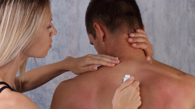 Sun protection. Man suffering from sunburn. ,woman applying sunburn lotion on man's back