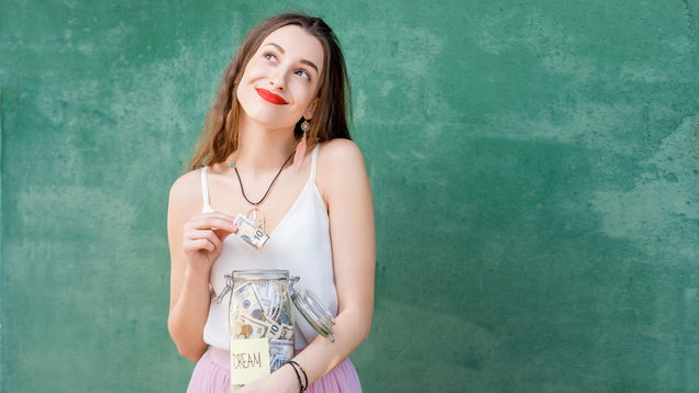 Woman holding a bottle full of money savings