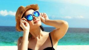 Young female fashion model smiling and wearing big sunglasses on a beach, sun protection and skincare concept.