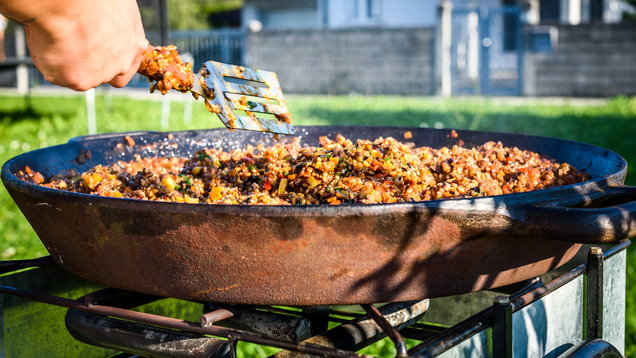 Cooking and making traditional Spanish Paella in iron cast pan.