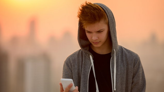 Teenager boy outdoors using mobile phone