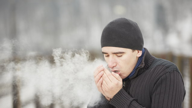 Man in black winter wear warming his hands with his breath