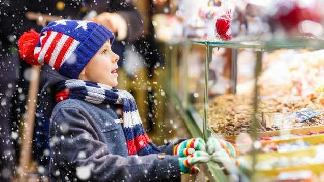 Little kid boy with gingerbread and sweets stand on Christmas ma