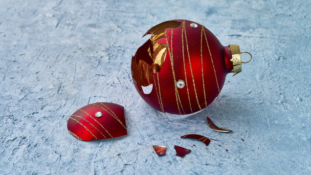 Broken Christmas ornaments on blue background.