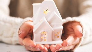 Female hands holding and saving small house