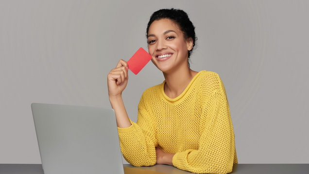 Happy woman with laptop holding credit card