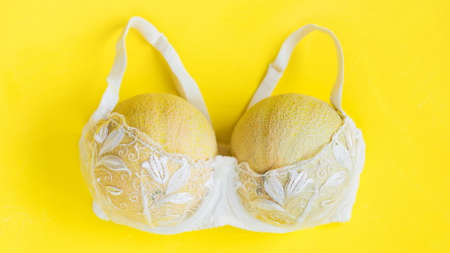 Breast enlargement concept, white bra with two melons on yellow background
