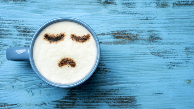 cup of cappuccino with a sad face