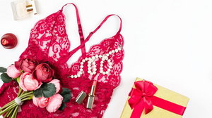 Women red lace lingerie with giftbox, flowers, make up items on white background. Postcard for Womens Day.