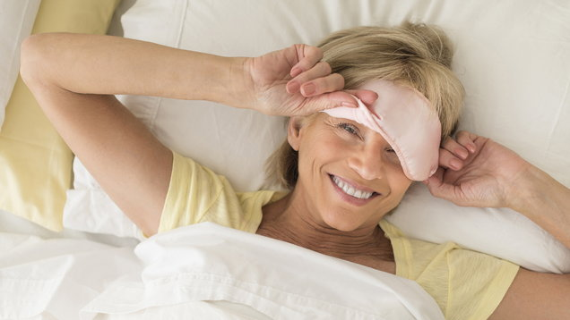 Happy Woman Wearing Sleep Mask On Bed
