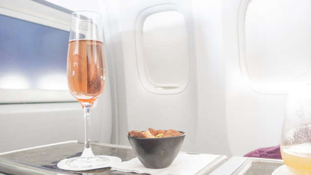 pink champagne and heated nuts in business class cabin, in flight, first class