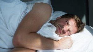 Caucasian mature man in white t-shirt does not want to get up in the morning