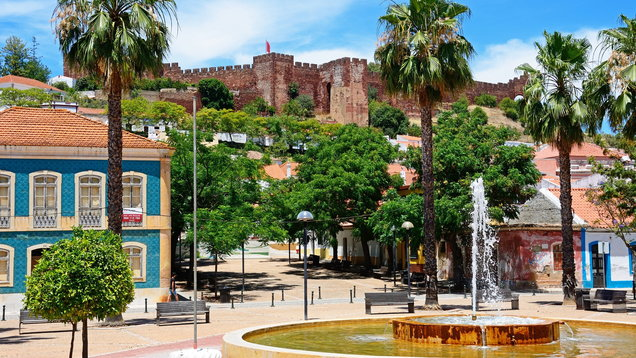 Fountain with castle to the rear, Silves, Portugal.
