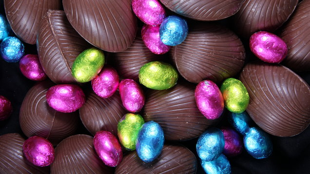 Pile of foil wrapped & unwrapped chocolate easter eggs in pink, blue & lime green.