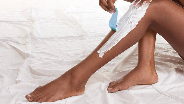 Woman shaving depilating her legs