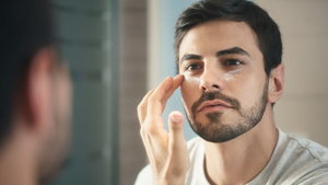 Young Man Applying Anti-aging Lotion fot Skin Care