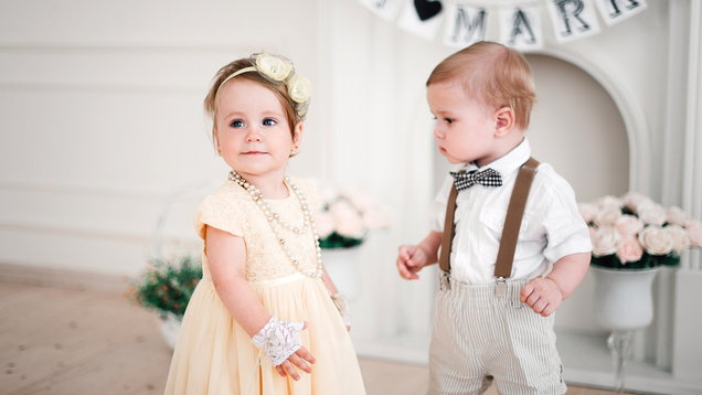 two babies wedding – boy and girl dressed as bride and groom