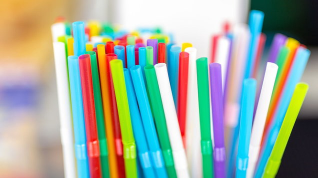Bunch of colorful plastic sipping straws in wooden box at cafe counter. Drinks decoration and accessories. Bright multicolored background