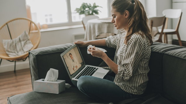 Woman with flu watching medical program on laptop