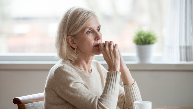 Thoughtful woman sitting at table with cup of tea