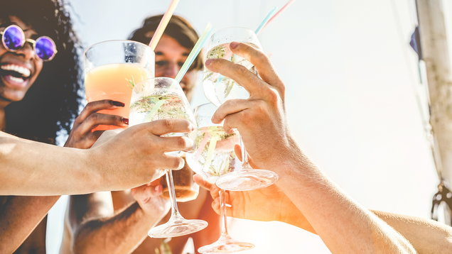 Group of happy friends cheering with tropical cocktails at boat party – Young people having fun in caribbean sea tour – Youth and summer vacation concept – Focus on bottom hands glass