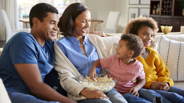 Toddler boy eating popcorn, sitting on the sofa with his sister and parents in their living room watching a movie together