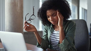 Overworked african business woman with headache at office