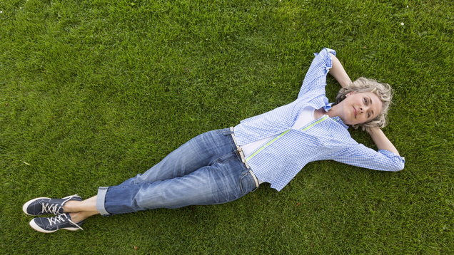 Middle-aged woman in casual weekend clothing relaxing on a grass lawn in a yard or park. She is smiling with a happy, contented expression and looks like she is daydreaming.