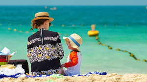 Two year old toddler boy with mother on beach